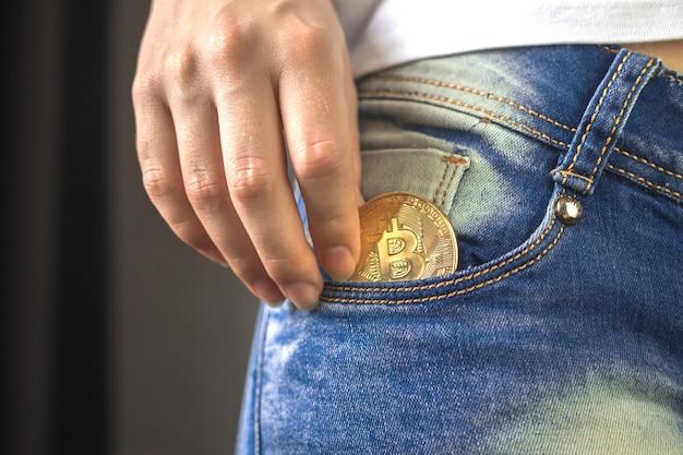Mão de uma mulher colocando bitcoin no bolso da calça jeans, moeda de criptomoeda dourada na foto do fundo do bolso