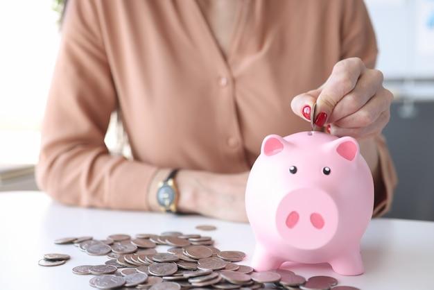 Mão de uma mulher colocando moedas no cofrinho rosa closeup