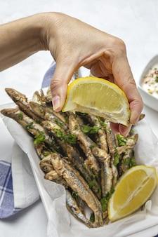 Mão de uma mulher com anchovas fritas com limão e salsa. conceito de frutos do mar