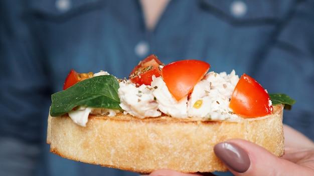 Mão de uma mulher com bruschetta de tomate cereja. aperitivo de vinho italiano.
