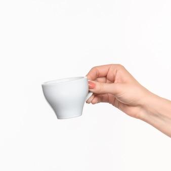 Mão de uma mulher com copo na parede branca