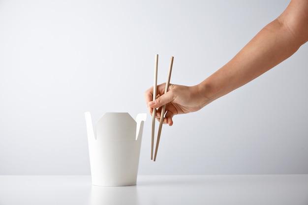 Mão de uma mulher com pauzinhos perto de uma caixa de takeway em branco com macarrão saboroso isolado no branco. apresentação do conjunto de varejo