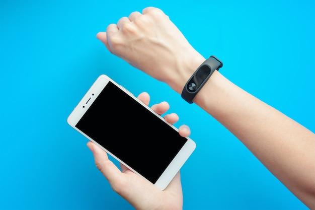 Mão de uma mulher com rastreador de aptidão e smartphone em fundo azul