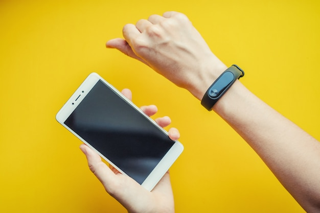 Mão de uma mulher com rastreador de fitness e smartphone