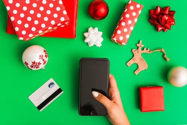Mão de uma mulher com smartphone perto de cartão de plástico e conjunto de decorações de natal