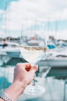 Mão de uma mulher com taça de vinho branco e champanhe em um fundo de marina de iates na frança