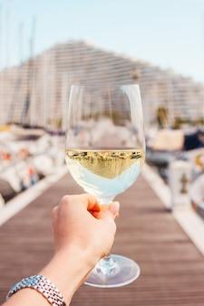 Mão de uma mulher com taça de vinho branco e champanhe em um píer.
