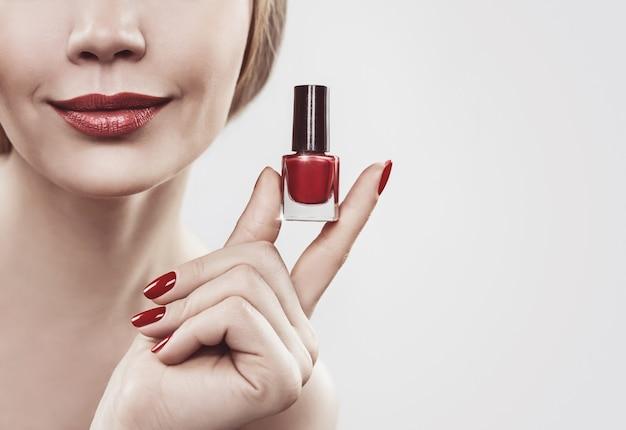 Mão de uma mulher com um frasco de esmalte vermelho. isolado em um fundo branco.