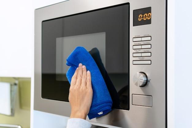 Mão de uma mulher com um pano de micro fibra limpando a superfície do forno de microondas. casa