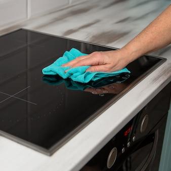 Mão de uma mulher com um pano de microfibra azul esfrega um fogão de cerâmica de vidro na cozinha.