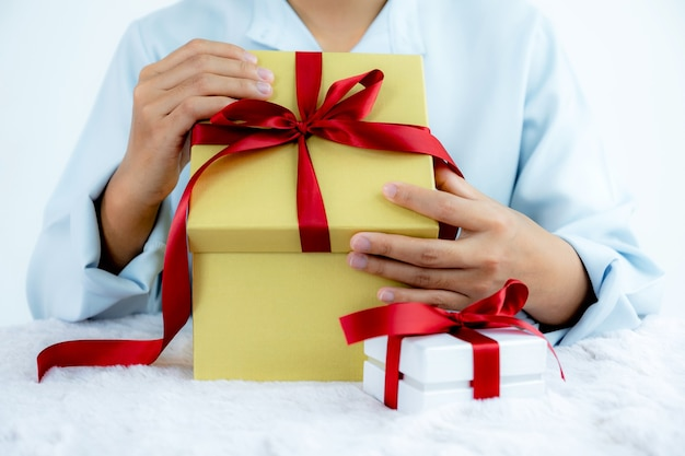 Mão de uma mulher com uma camisa azul abrindo uma caixa de ouro amarrada com uma fita vermelha presente para o festival de dar feriados especiais como natal, dia dos namorados.
