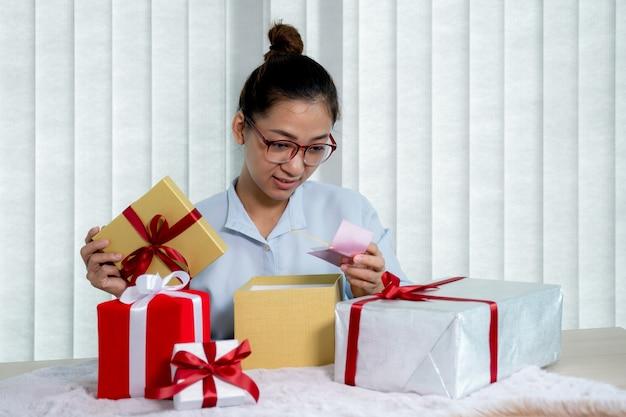Mão de uma mulher com uma camisa azul abrindo uma caixa de presente de ouro amarrada com uma fita vermelha e um cartão vermelho presente para o festival de dar feriados especiais como natal, dia dos namorados.