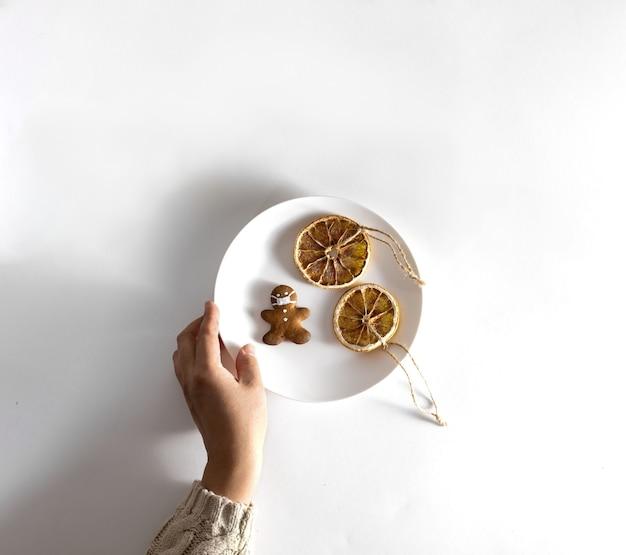 Mão de uma mulher com uma camisola de malha segura um prato de doces de natal. cookies em forma de um homem com uma máscara e fatias de laranja secas com canela.