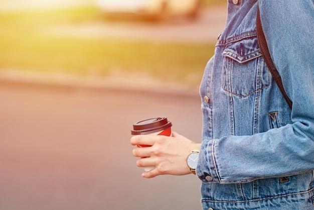 Mão de uma mulher com uma xícara de café de papel levar em uma rua da cidade