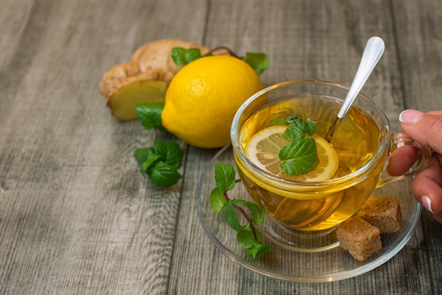 Mão de uma mulher com uma xícara de chá de gengibre, limão e açúcar mascavo em madeira cinza