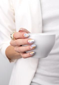 Mão de uma mulher com unhas de cor pastel na moda segurando xícara