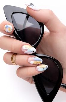 Mão de uma mulher com unhas na moda segurando óculos de sol