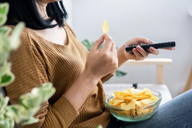 Mão de uma mulher comendo batatas fritas e segurando uma tv no controle remoto
