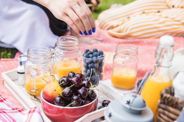 Mão de uma mulher comendo mirtilo com jarra de suco de manga e frutas