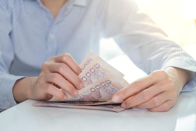 Mão de uma mulher contando dinheiro das notas da tailândia