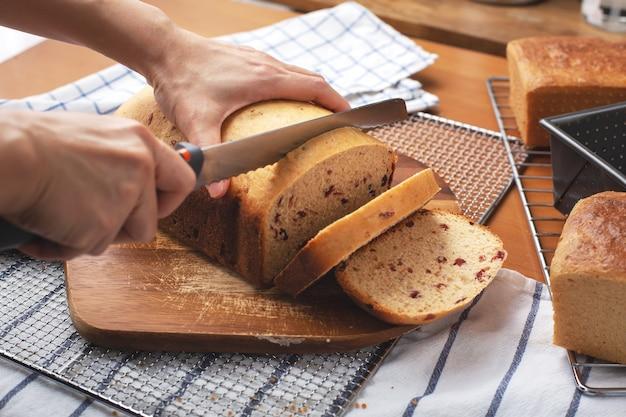 Mão de uma mulher cortando pão fresco de cranberry