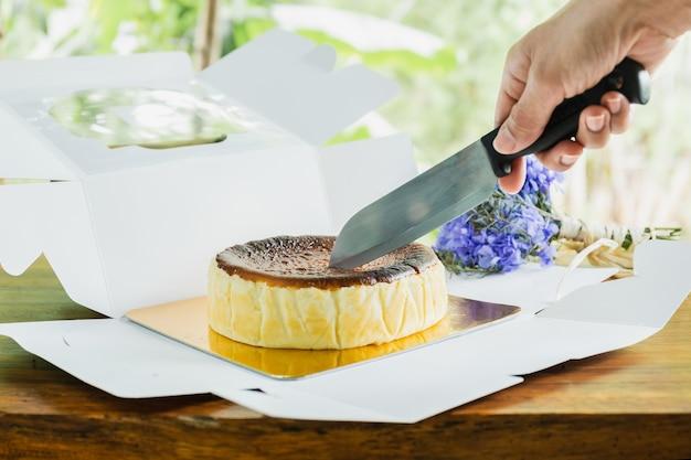 Mão de uma mulher corte o cheesecake queimado basco com a faca na mesa de madeira.