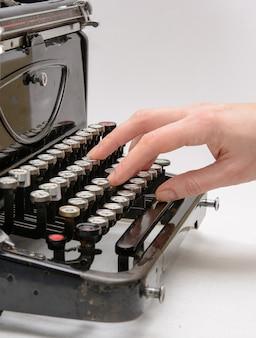 Mão de uma mulher digitando com uma velha máquina de escrever vintage