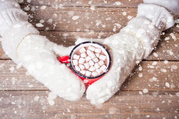 Mão de uma mulher em luvas brancas, segurando uma caneca vermelha de cacau de natal com marshmallows.