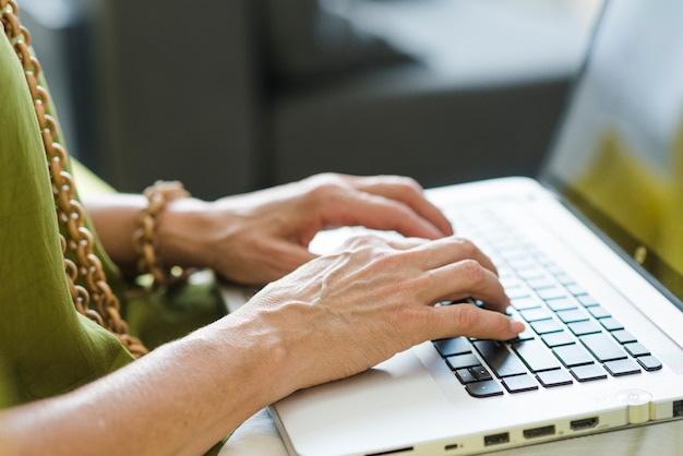 Mão de uma mulher envelhecida digitando no laptop