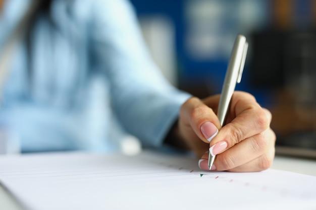 Mão de uma mulher escrevendo com uma caneta esferográfica prateada em close do caderno