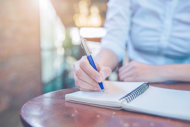 Mão de uma mulher escrevendo em um bloco de notas com uma caneta no escritório