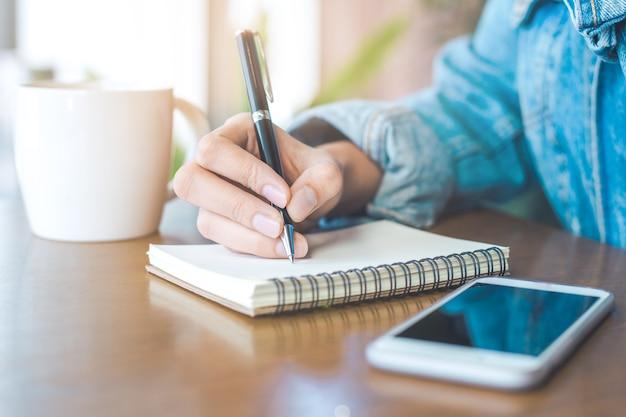 Mão de uma mulher escrevendo em um bloco de notas com uma caneta