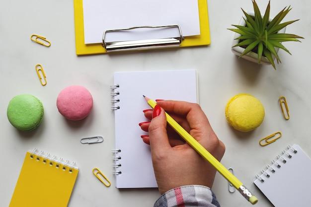 Mão de uma mulher escrevendo em um bloco de notas ou caderno