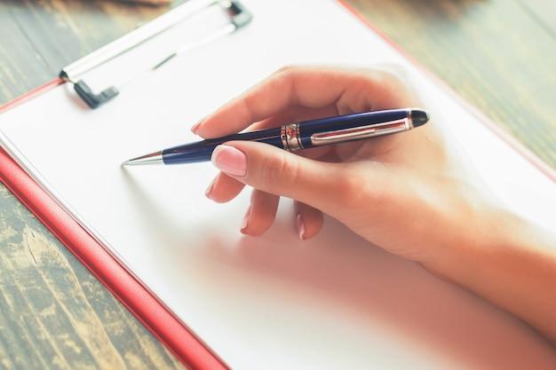 Mão de uma mulher escrevendo em um planejador em branco no café.