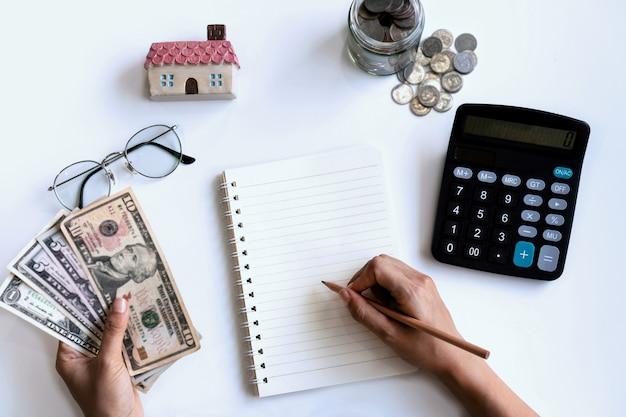 Mão de uma mulher escrevendo no caderno enquanto segura o dinheiro e a calculadora do lado dela. conceito de orçamento doméstico.