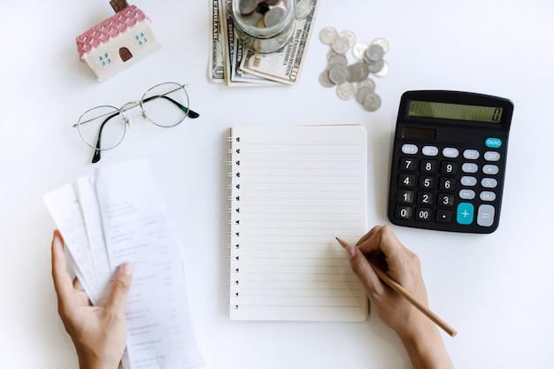 Mão de uma mulher escrevendo no caderno, mantendo as contas e calculadora do lado dela. copie o espaço, vista superior. conceito de orçamento em casa.