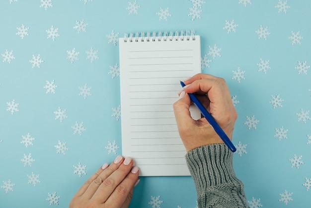 Mão de uma mulher escrevendo no caderno vazio decorado com enfeites de natal