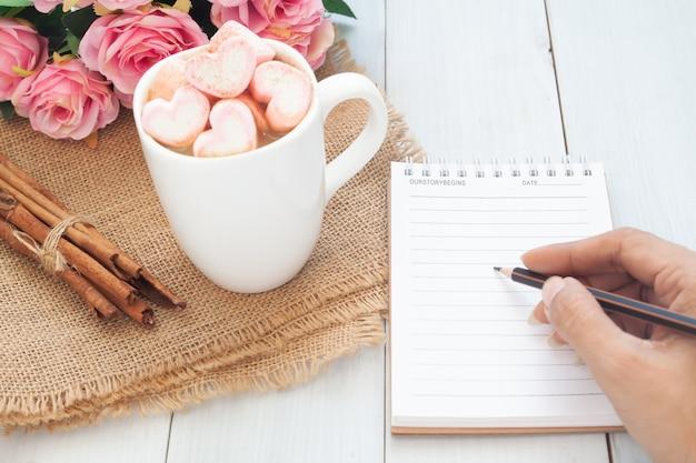 Mão de uma mulher escrevendo no notebook com bela bebida quente na mesa