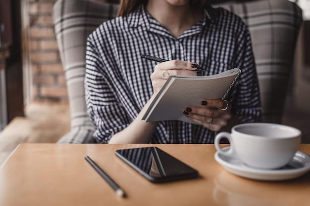Mão de uma mulher escrevendo o bloco de notas na mesa de madeira na cafeteria