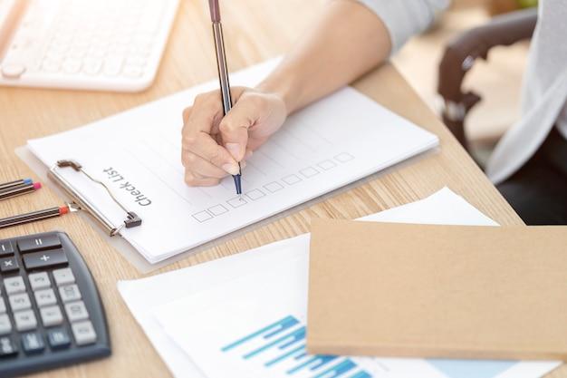 Mão de uma mulher escrevendo papel de lista de verificação, conceito de planejamento de memorando. papelada para preencher informações em negócios.