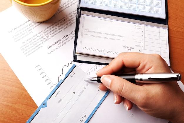 Mão de uma mulher escrevendo um cheque - close-up