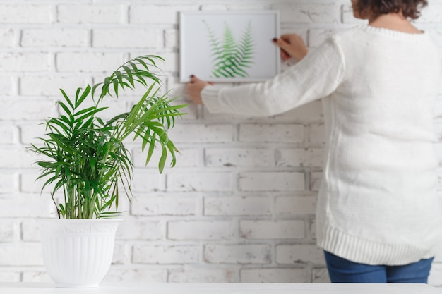 Mão de uma mulher está segurando a moldura e pote de concreto com planta em casa
