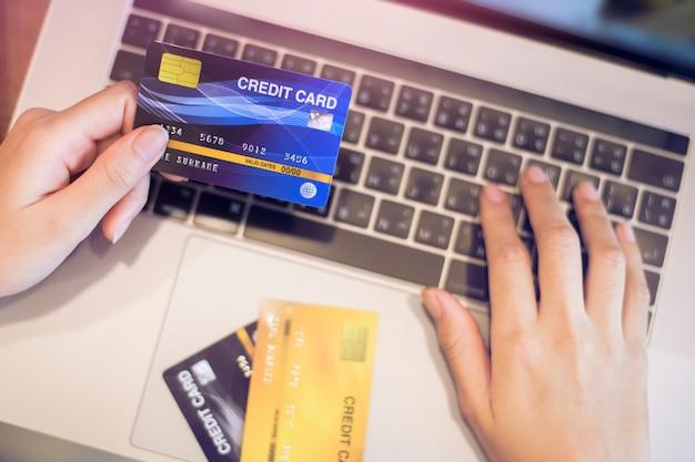 Mão de uma mulher está segurando o cartão de crédito, compras on-line