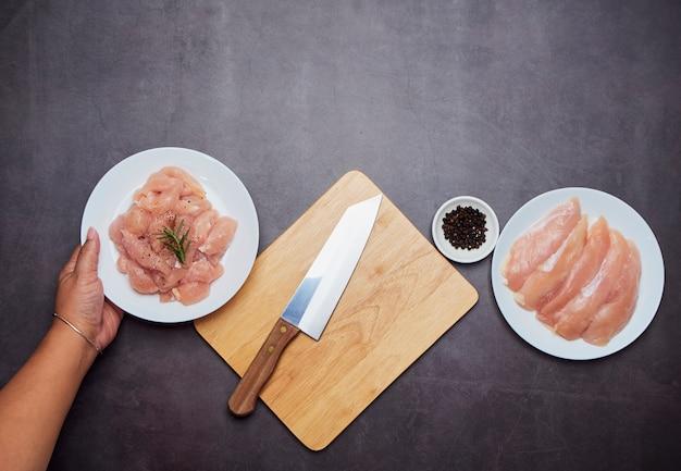 Mão de uma mulher está segurando o prato com frango fresco