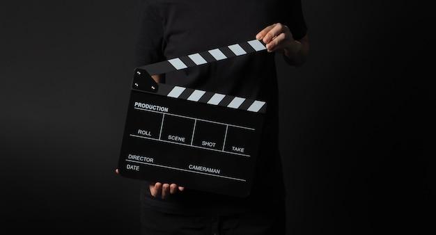 Mão de uma mulher está segurando uma claquete preta sobre fundo preto. no estúdio de filmagem.