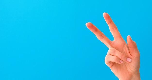 Mão de uma mulher fazendo sinal de vitória isolado em azul