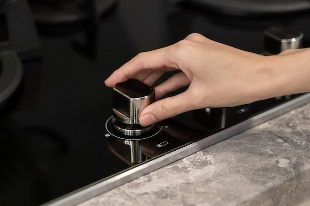 Mão de uma mulher girando o botão do interruptor no fogão a gás na cozinha.