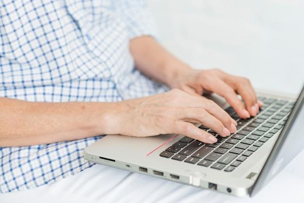Mão de uma mulher idosa digitando no laptop portátil