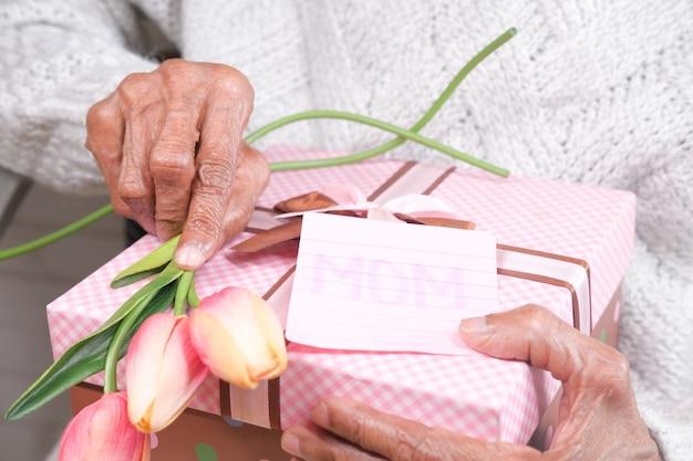 Mão de uma mulher idosa segurando um presente e uma flor
