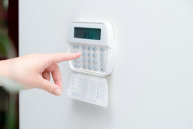 Mão de uma mulher inserindo a senha do sistema de alarme de um apartamento, casa de escritório. vigilância e console de proteção contra borracha e ladrão
